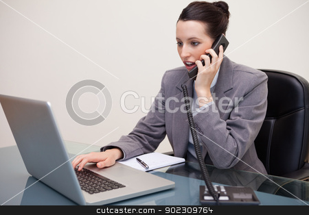 Businesswoman typing on laptop while talking on the phone stock photo, Young businesswoman typing on laptop while talking on the phone by Wavebreak Media