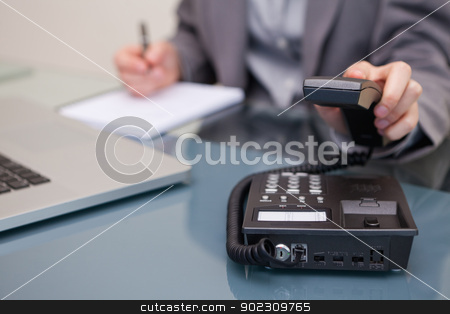 Telephone being hung up by businesswoman stock photo, Telephone being hung up by young businesswoman by Wavebreak Media