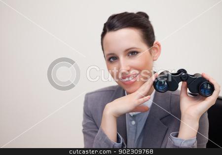 Smiling businesswoman with binoculars stock photo, Smiling young businesswoman with binoculars by Wavebreak Media