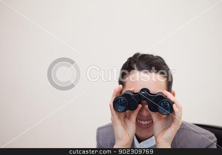 Businesswoman looking through binoculars stock photo, Young businesswoman looking through binoculars by Wavebreak Media