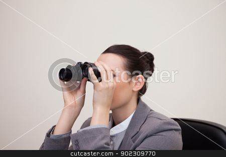 Businesswoman having a look through binoculars stock photo, Young businesswoman having a look through binoculars by Wavebreak Media
