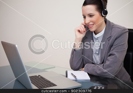 Businesswoman with headset on her laptop stock photo, Young businesswoman with headset on her laptop by Wavebreak Media