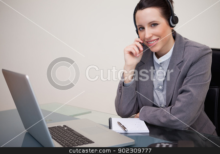 Smiling businesswoman with headset on her laptop stock photo, Smiling young businesswoman with headset on her laptop by Wavebreak Media