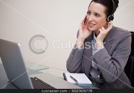 Businesswoman with headset sitting at her desk stock photo, Young businesswoman with headset sitting at her desk by Wavebreak Media