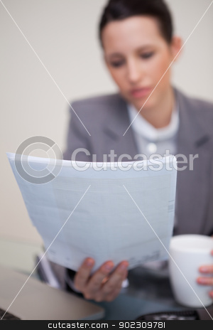 Contract being read by businesswoman stock photo, Contract being read by young businesswoman by Wavebreak Media