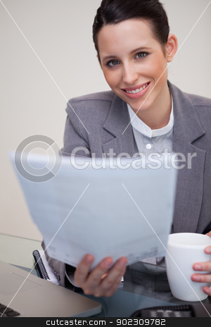 Smiling businesswoman holding contract stock photo, Smiling young businesswoman holding contract by Wavebreak Media