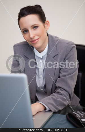 Businesswoman working at her desk stock photo, Young businesswoman working at her desk by Wavebreak Media