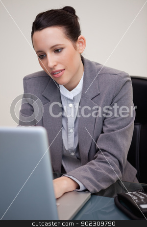 Businesswoman working on her laptop stock photo, Young businesswoman working on her laptop by Wavebreak Media