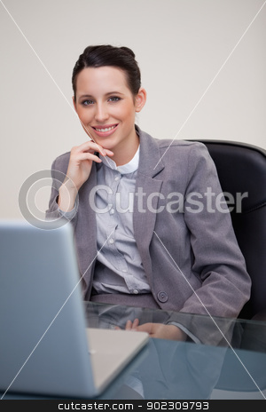 Smiling businesswoman sitting in her office stock photo, Smiling young businesswoman sitting in her office by Wavebreak Media