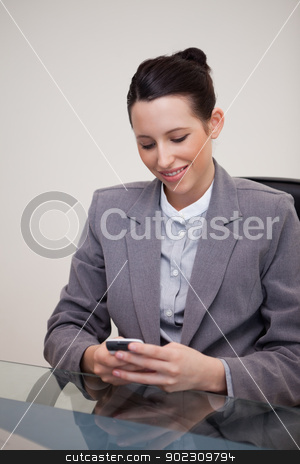 Smiling businesswoman sitting behind desk writing a textmessage stock photo, Smiling young businesswoman sitting behind desk writing a textmessage by Wavebreak Media