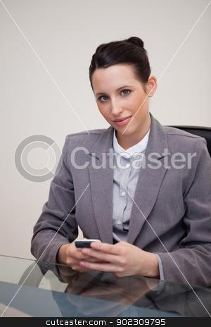 Businesswoman behind desk with cellphone stock photo, Young businesswoman behind desk with cellphone by Wavebreak Media