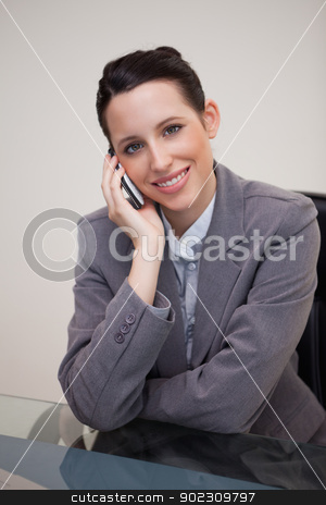 Smiling businesswoman having a call on her cellphone stock photo, Smiling young businesswoman having a call on her cellphone by Wavebreak Media