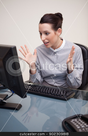Businesswoman seems to be surprised by computer stock photo, Young businesswoman seems to be surprised by computer by Wavebreak Media