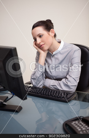 Businesswoman waiting patiently for her pc to work stock photo, Young businesswoman waiting patiently for her pc to work by Wavebreak Media