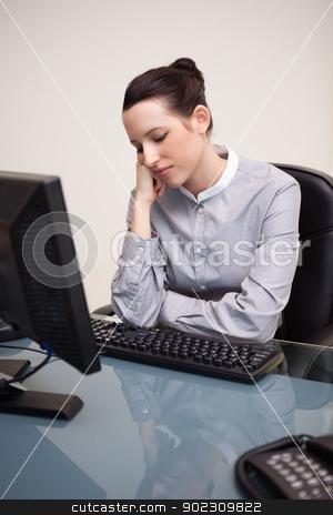 Businesswoman sitting bored at her desk stock photo, Young businesswoman sitting bored at her desk by Wavebreak Media