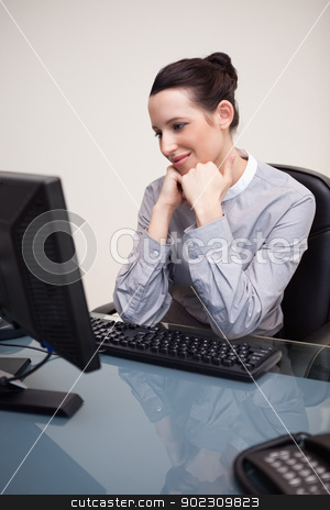 Happy smiling businesswoman sitting at her desk stock photo, Happy smiling young businesswoman sitting at her desk by Wavebreak Media