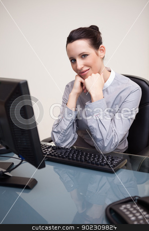 Smiling businesswoman waiting patiently at her computer stock photo, Smiling young businesswoman waiting patiently at her computer by Wavebreak Media