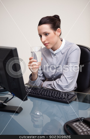 Businesswoman at her desk with a glass of water stock photo, Young businesswoman at her desk with a glass of water by Wavebreak Media