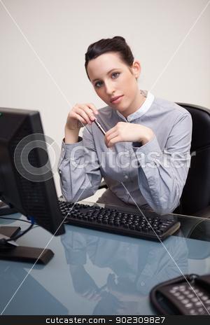 Businesswoman holding pen sitting behind a desk stock photo, Young businesswoman holding pen sitting behind a desk by Wavebreak Media