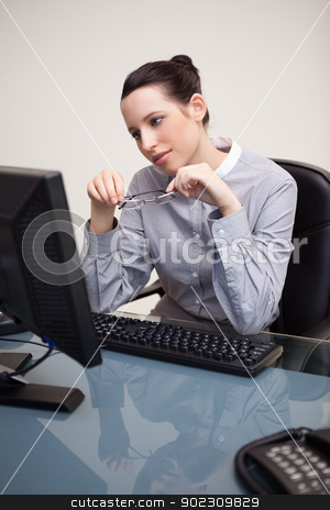 Businesswoman looking at screen holding her glasses stock photo, Young businesswoman looking at screen holding her glasses by Wavebreak Media