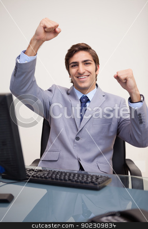 Businessman raising his fists in success stock photo, Young businessman raising his fists in success by Wavebreak Media