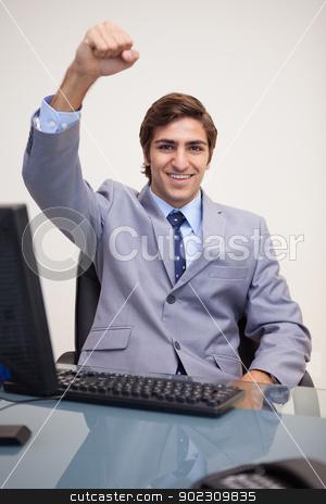 Businessman raising his fist in success stock photo, Young businessman raising his fist in success by Wavebreak Media