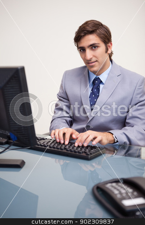 Businessman typing on his keyboard stock photo, Young businessman typing on his keyboard by Wavebreak Media