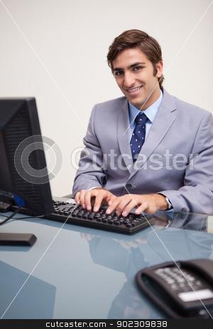 Smiling businessman typing on his keyboard stock photo, Smiling young businessman typing on his keyboard by Wavebreak Media