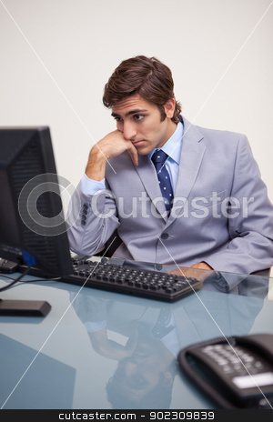 Businessman waiting for his computer to work stock photo, Young businessman waiting for his computer to work by Wavebreak Media