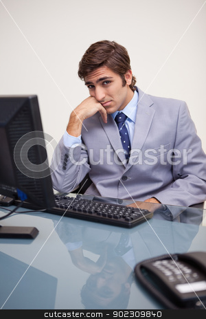 Businessman sitting bored at his workplace stock photo, Young businessman sitting bored at his workplace by Wavebreak Media
