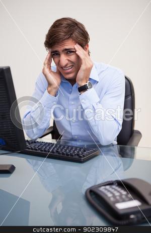 Businessman having a headache in his office stock photo, Young businessman having a headache in his office by Wavebreak Media