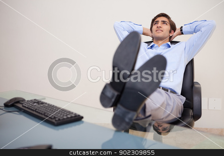 Businessman leaning back in his chair stock photo, Young businessman leaning back in his chair by Wavebreak Media