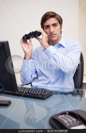 Businessman with binoculars in his office stock photo, Young businessman with binoculars in his office by Wavebreak Media