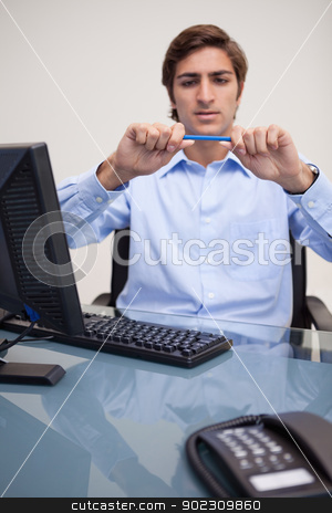 Businessman about to break his pencil stock photo, Young businessman about to break his pencil by Wavebreak Media