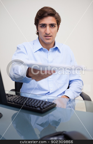 Businessman handing over paperwork stock photo, Young businessman handing over paperwork by Wavebreak Media