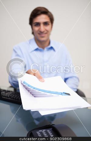 Statistics being handed over by businessman stock photo, Statistics being handed over by young businessman by Wavebreak Media