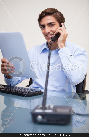 Smiling businessman holding paperwork while on the phone stock photo, Smiling young businessman holding paperwork while on the phone by Wavebreak Media
