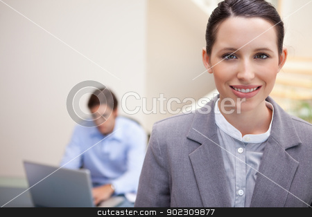 Smiling businesswoman with colleague working on his laptop behin stock photo, Smiling young businesswoman with colleague working on his laptop behind her by Wavebreak Media