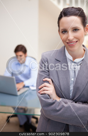 Smiling businesswoman with colleague on his laptop behind her stock photo, Smiling young businesswoman with colleague on his laptop behind her by Wavebreak Media