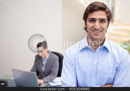 Smiling businessman with colleague on her laptop behind him stock photo, Smiling young businessman with colleague on her laptop behind him by Wavebreak Media