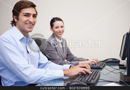 Side view of smiling colleagues working next to each other stock photo, Side view of smiling young colleagues working next to each other by Wavebreak Media