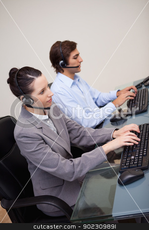 Side view of call center agents at work stock photo, Side view of young call center agents at work by Wavebreak Media