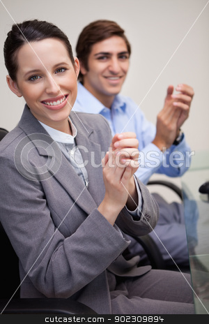 Side view of business team clapping while sitting at desk stock photo, Side view of young business team clapping while sitting at desk by Wavebreak Media