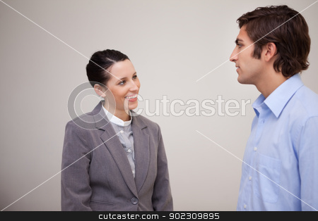 Businesswoman smiling at her colleague stock photo, Young businesswoman smiling at her colleague by Wavebreak Media