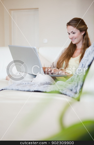 Side view of smiling woman working on her laptop on the sofa stock photo, Side view of smiling young woman working on her laptop on the sofa by Wavebreak Media