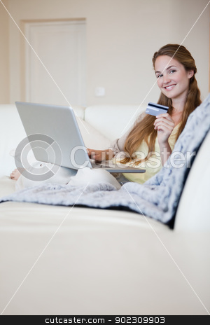 Woman on the sofa booking a flight online stock photo, Young woman on the sofa booking a flight online by Wavebreak Media