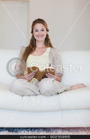 Woman enjoys reading a book on her couch stock photo, Young woman enjoys reading a a book on her couch by Wavebreak Media
