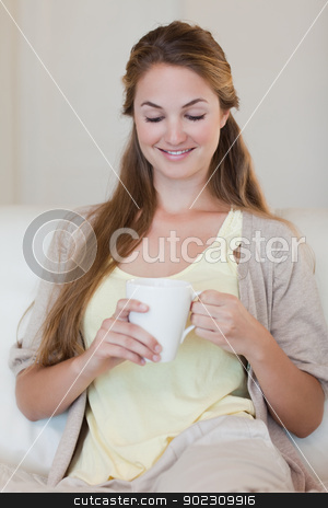 Woman enjoys having a coffee on her couch stock photo, Young woman enjoys having a coffee oh her couch by Wavebreak Media