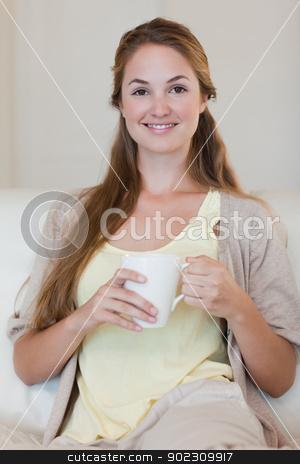 Woman having coffee on her sofa stock photo, Young woman having coffee on her sofa by Wavebreak Media