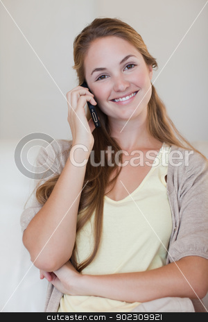 Smiling woman having a conversation on her cellphone stock photo, Smiling young woman having a conversation on her cellphone by Wavebreak Media
